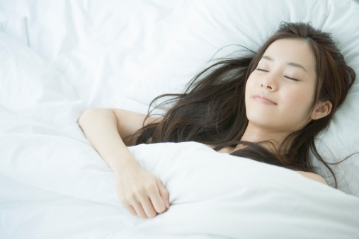 Young woman sleeping on bed, portrait